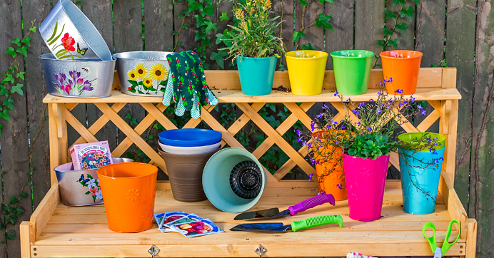 Garden bench with pots, planters, gloves, and gardening tools