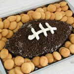 Championship games are upon us and it's time to prep the game day snack menu! Along with the savory, I always love to serve something sweet. Combine smooth cream cheese, peanut butter, cool whip, and peanuts for a crunch! Shape into a football and cover with chocolate sprinkles. Finish it with cool whip laces and serve with sweet wafers, graham crackers, or pretzels for the ultimate sweet and salty pair. This recipe will be a touch down for your game day guests! Here's What You'll Need: 1 Cup of Cream Cheese, Softened 1 Cup of Smooth Peanut Butter 8-oz. Container of Cool Whip, Divided 1 Cup of Roasted Peanuts ½ Cup Chocolate Sprinkles Plastic Wrap Vanilla Wafers, Pretzels, or Graham Crackers for dipping Score a Towndown with This Dip! Combine the cream cheese, peanut butter, cool whip (reserving ¼ cup aside), and peanuts in a large mixing bowl with a spatula until smooth. Wrap the mixture in plastic wrap and refrigerate for 30 minutes. Remove from the wrap and use hands to press the mixture into a football shape on a flat serving platter. Press the chocolate sprinkles into the side of the football, surrounding it completely. Use a spoon or piping bag to create laces with the remaining cool whip on the center of the football. Surround the dip with vanilla wafer, pretzels, or graham crackers for dipping. Looking for another savory dip this football season? Try out this peanut butter gingersnap football dip!
